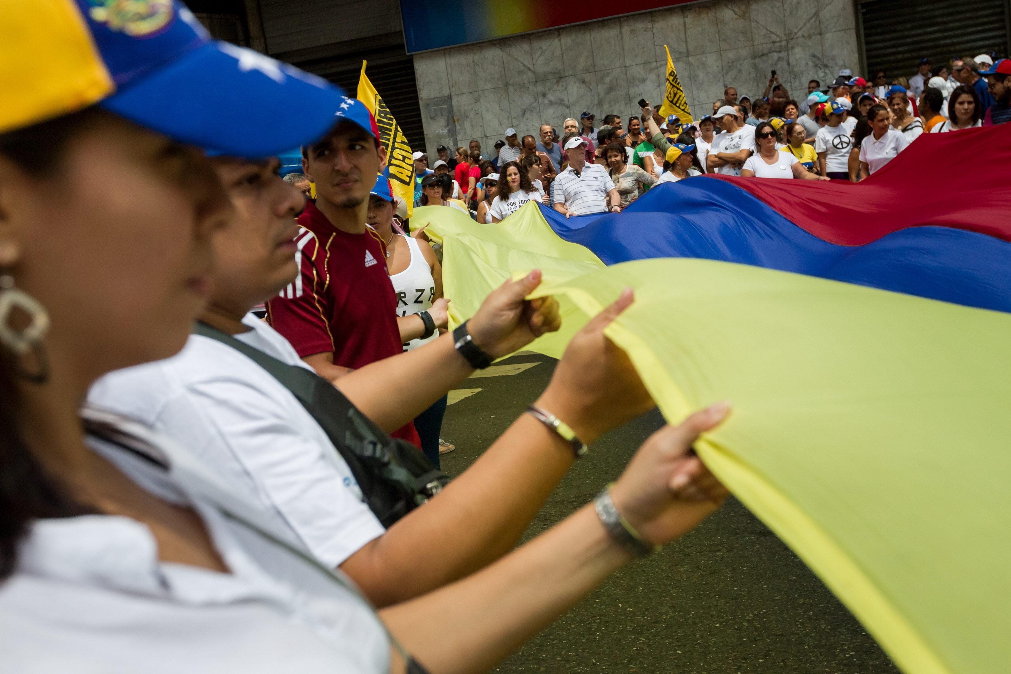 CAR01. CARACAS (VENEZUELA),19/9/2015 , Un grupo de personas ondean una bandera venezolana hoy, sábado 19 de septiembre del 2015, en la ciudad de Caracas (Venezuela). La oposición venezolana se moviliza en 22 ciudades del país para dar comienzo a la campaña 'Venezuela quiere' de cara a las legislativas de diciembre y en apoyo de Leopoldo López, uno de sus integrantes, condenado hace unos días a cerca de 14 años de prisión. EFE/MIGUEL GUTIÉRREZ