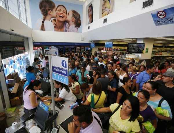 REFILE - UPDATING SECOND SENTENCE  People line up to buy hygienic products inside a Farmatodo drugstore in Caracas February 3, 2015.  Authorities are pressing charges against Venezuelan pharmacy chain Farmatodo for not opening enough check-out counters, with its executives summoned for questioning over the weekend.  REUTERS/Jorge Silva (VENEZUELA - Tags: BUSINESS SOCIETY)
