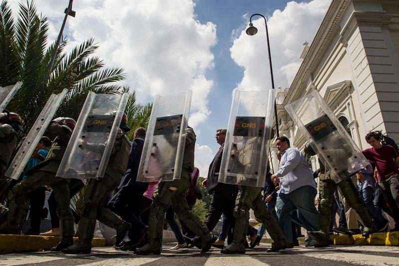 Miembros de la Guardia Nacional Bolivariana (GNB) custodian el paso de los diputados de la Asamblea Nacional al culminar la sesión del día de hoy, jueves 27 de octubre de 2016, en Caracas (Venezuela). La Asamblea Nacional desarrolló hoy una sesión en la que sus miembros discutieron la participación de los gremios académicos y ciudadanos en lo que la mayoría opositora, que controla el Parlamento, denomina como la defensa de la Constitución. EFE/MIGUEL GUTIÉRREZ