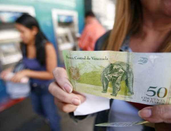 CAR03 - CARACAS (VENEZUELA), 02/01/08 .- Una mujer sostiene la nueva moneda de Venezuela, hoy, 2 de enero de 2008, en Caracas, el bolívar fuerte, que inició ayer, 1 de enero, su andadura con la puesta en circulación de una serie de trece flamantes denominaciones, seis billetes y siete monedas, que quitan tres ceros al antiguo bolívar. EFE/David Fernandez