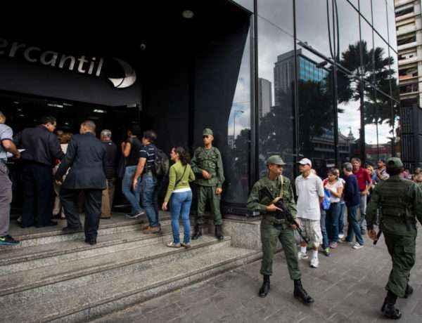 CAR20. CARACAS (VENEZUELA), 13/12/2016.- Un grupo de personas aguarda para realizar transacciones bancarias hoy, 13 de diciembre de 2016, en Caracas (Venezuela). Miles de venezolanos acudieron hoy a las entidades bancarias públicas y privadas del país para despojarse de sus billetes de 100 bolívares, el de más alta denominación en la moneda local, que perderá su valor y dejará de circular el jueves por orden del presidente del país, Nicolás Maduro. EFE/MIGUEL GUTIERREZ