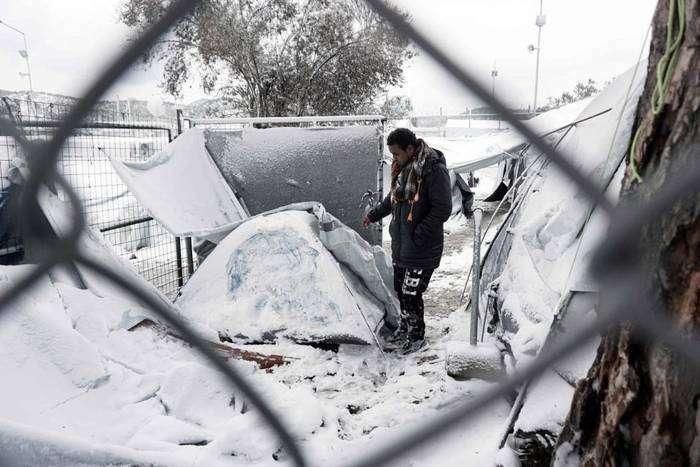 Un inmigrante junto a una tienda cubierta de nieve en Moria, en la isla de Lesbos en Grecia. Foto: AFP.
