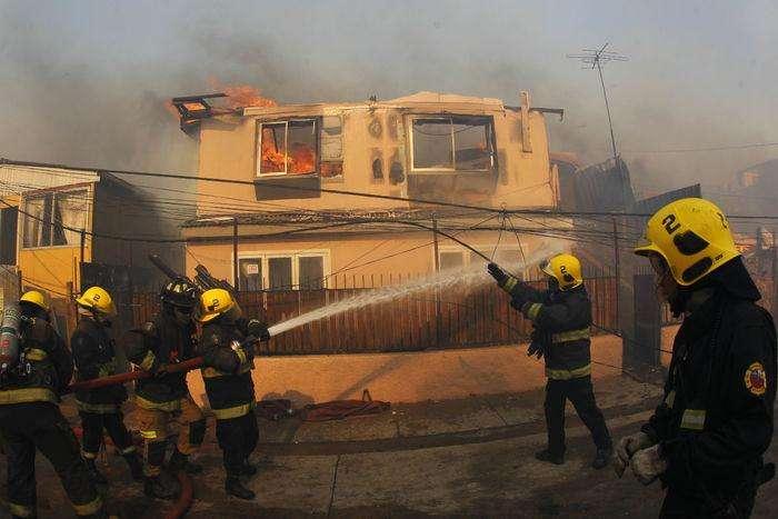 CH01. VALPARAISO (CHILE), 02/01/2017.- Personal de bomberos combate un incendio forestal en el sector de Playa Ancha en la ciudad de Valparaíso (Chile) hoy, 2 de enero de 2016, que afectó a viviendas y vecinos del sector. Un incendio forestal que estalló hoy en la parte alta del puerto chileno de Valparaíso llevó a las autoridades a declarar alerta roja en la ciudad y a disponer la evacuación preventiva de unas 25 viviendas próximas al foco de fuego, informaron fuentes oficiales.