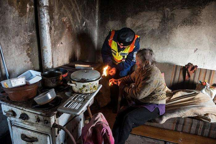El agente de policía Attila Biszku enciende la estufa en la vivienda de una mujer sin recursos en Nagycserkesz (Hungría), el 6 de enero de 2017. Debido a las bajas temperaturas que se registran estos días, las autoridades de la región visitan a las personas más ancianas y con una situación más vulnerable para asegurarse de que no sufran hipotermia a causa del frío. Foto: EFE