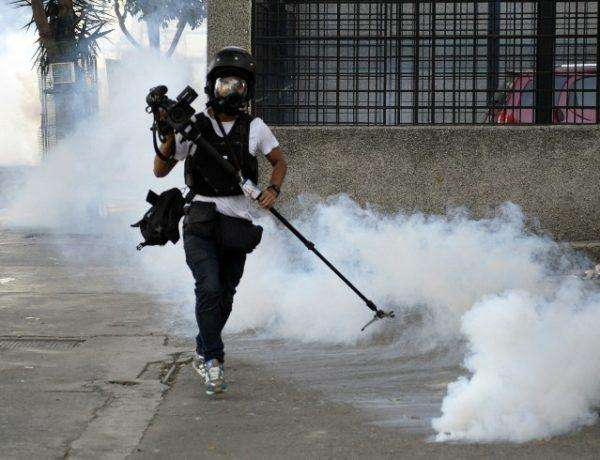 Cameraman runs away from tear gas during an anti-government protest in Caracas on February 22, 2014. Hundreds of thousands of Venezuelans took to the streets of Caracas in marches for and against President Nicolas Maduro's government Saturday, as the nation's massive divide became ever more evident. The protests -- which began on February 4 -- are seen as the biggest test yet to socialist leader Maduro since he succeeded late leftist icon Hugo Chavez last year, with the country's economic problems at the heart of often bloody marches that have left 10 people dead and scores injured. AFP PHOTO/ JUAN BARRETO
