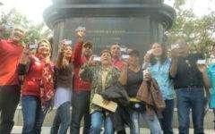 Grupo de personas muestran su Carnet de la patria frente a la estatua del Libertador en la Plaza Bolívar.