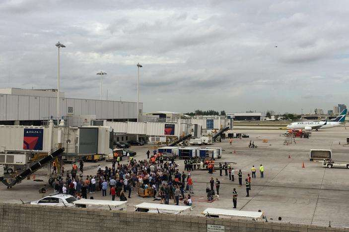 Travelers are evacuated out of the terminal and onto the tarmac after airport shooting at Fort Lauderdale-Hollywood International Airport in Florida, U.S., January 6, 2017.   REUTERS/Zachary Fagenson