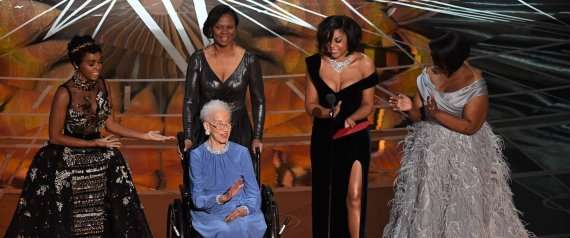 NASA physicist Katherine Johnson (C) is surrounded by US singer and actress Janelle Monae (L), US actress Taraji P. Henson (2ndR) and US actress Octavia Spencer (R) as they present on stage the Best Documentary Feature award at the 89th Oscars on February 26, 2017 in Hollywood, California. / AFP PHOTO / Mark RALSTON