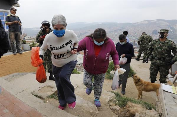 Militares colombianos suministran alimentos a pobladores de la localida Soacha, el 30 de marzo