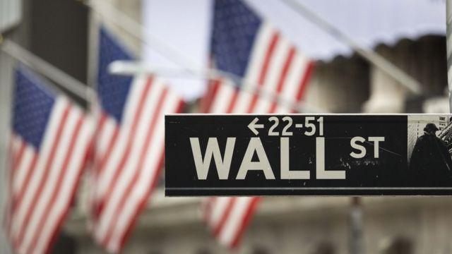 Cartel de la calle Wall Street en Nueva York con un fondo de banderas de Estados Unidos