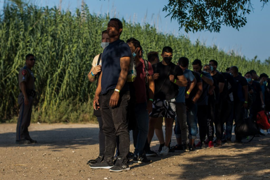 Luego de identificarse con las autoridades, este grupo de migrantes venezolanos espera en fila para su traslado a un centro de procesamiento de ICE